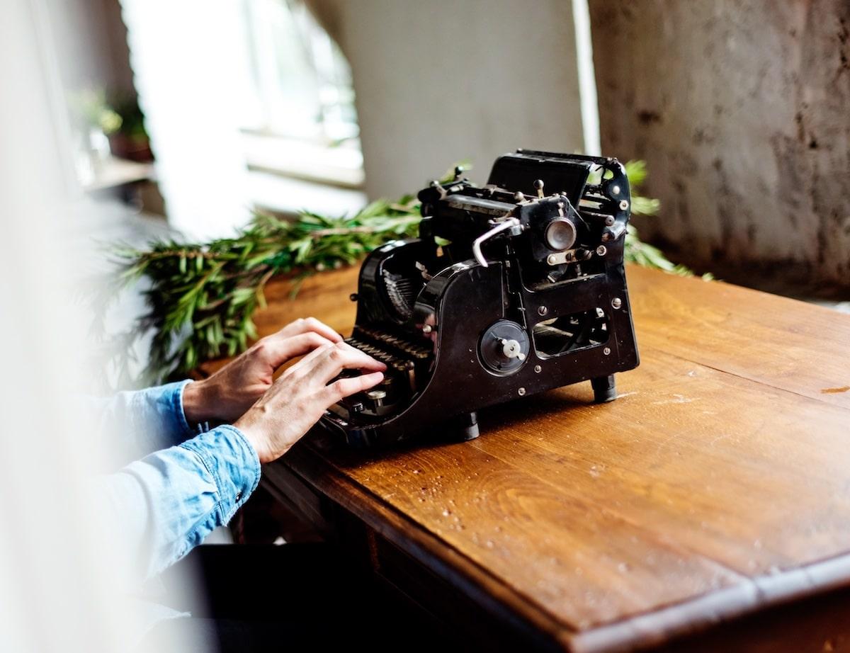 Des mains tapent sur une très ancienne machine à écrire