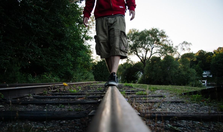 Un homme marche sur des rails