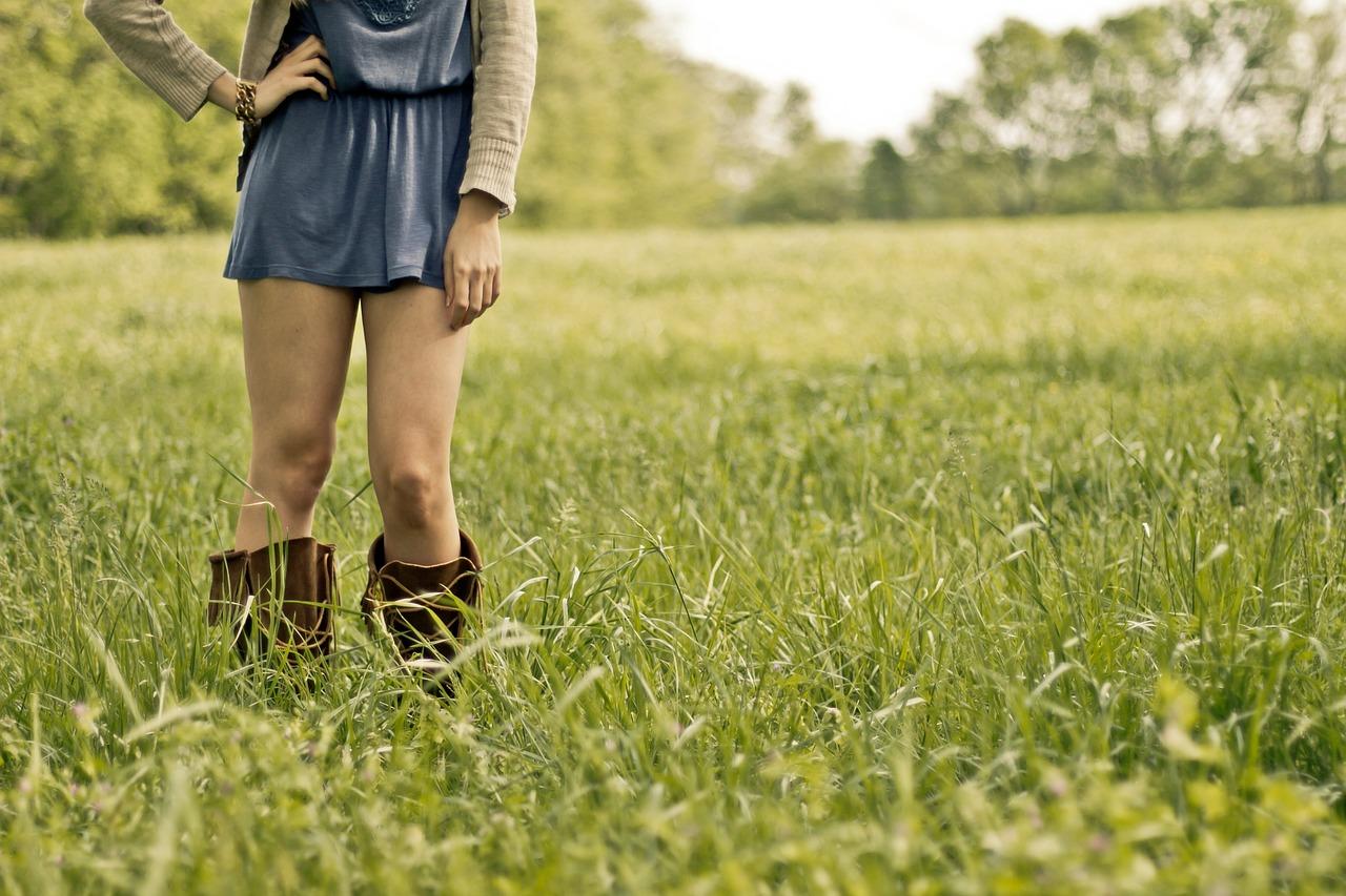 Une femme en botte dans un champ