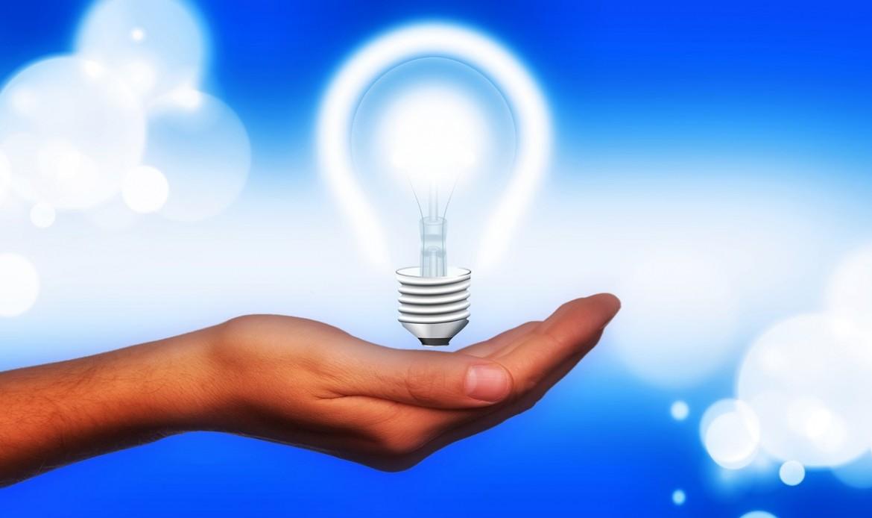 Un main tient une ampoule allumée