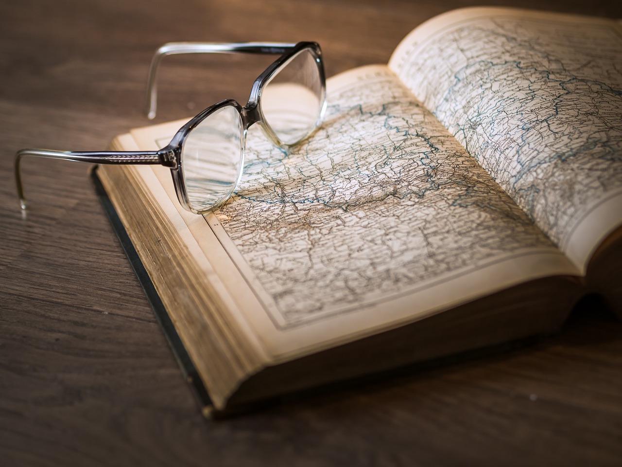 Un livre ouvert avec des lunettes posées dessus