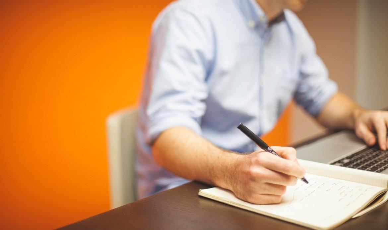 Un homme écrit sur un carnet à son poste de travail