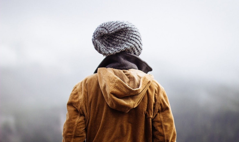 Un personnage avec un bonnet, de dos, regarde la brume