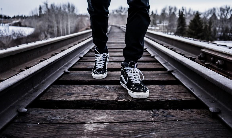 Un homme marche sur des rails en hiver