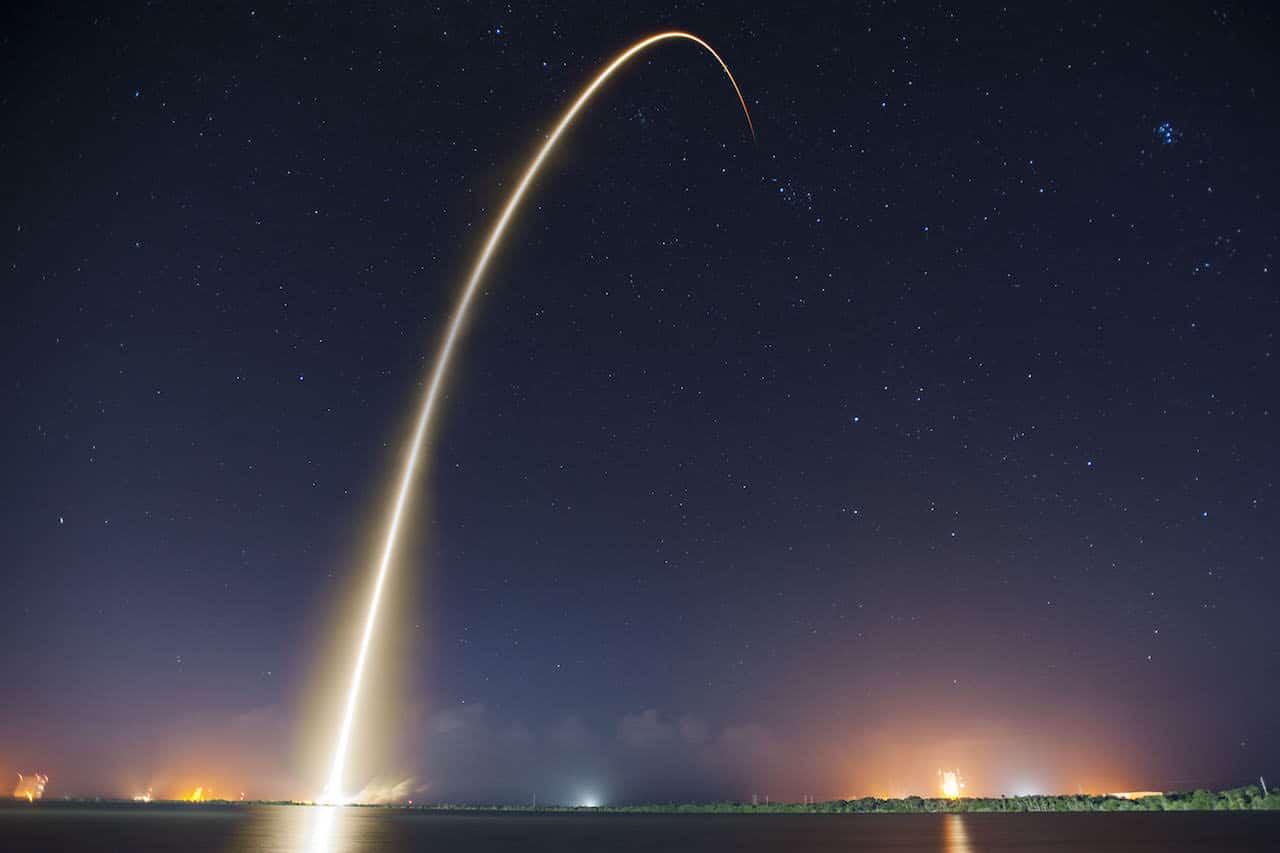 Une fusée vient d'être tirée et trace une ligne de lumière dans la nuit