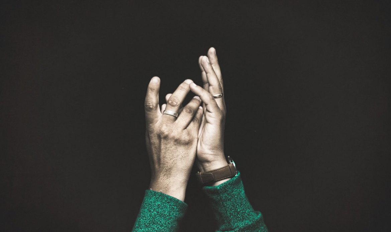 Un homme noir tend ses mains vers le ciel