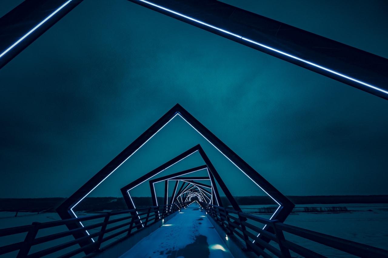 Un pont de nuit traverse de forme artistiques le long d'une plage