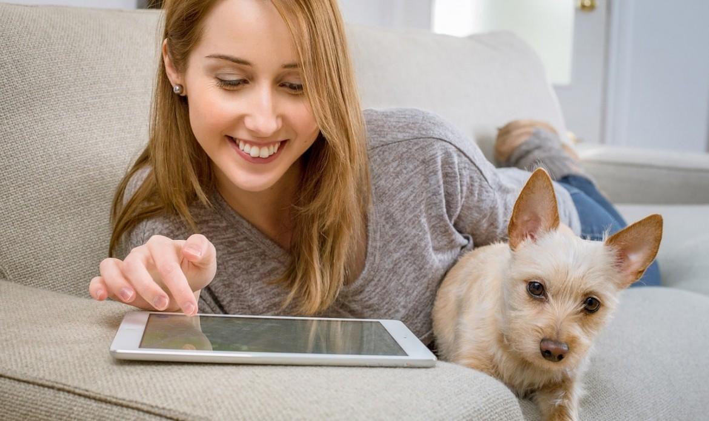 Une femme regarde sa tablette à côté de son chien