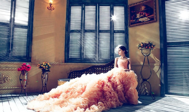 Une femme porte une somptueuse robe rose saumon