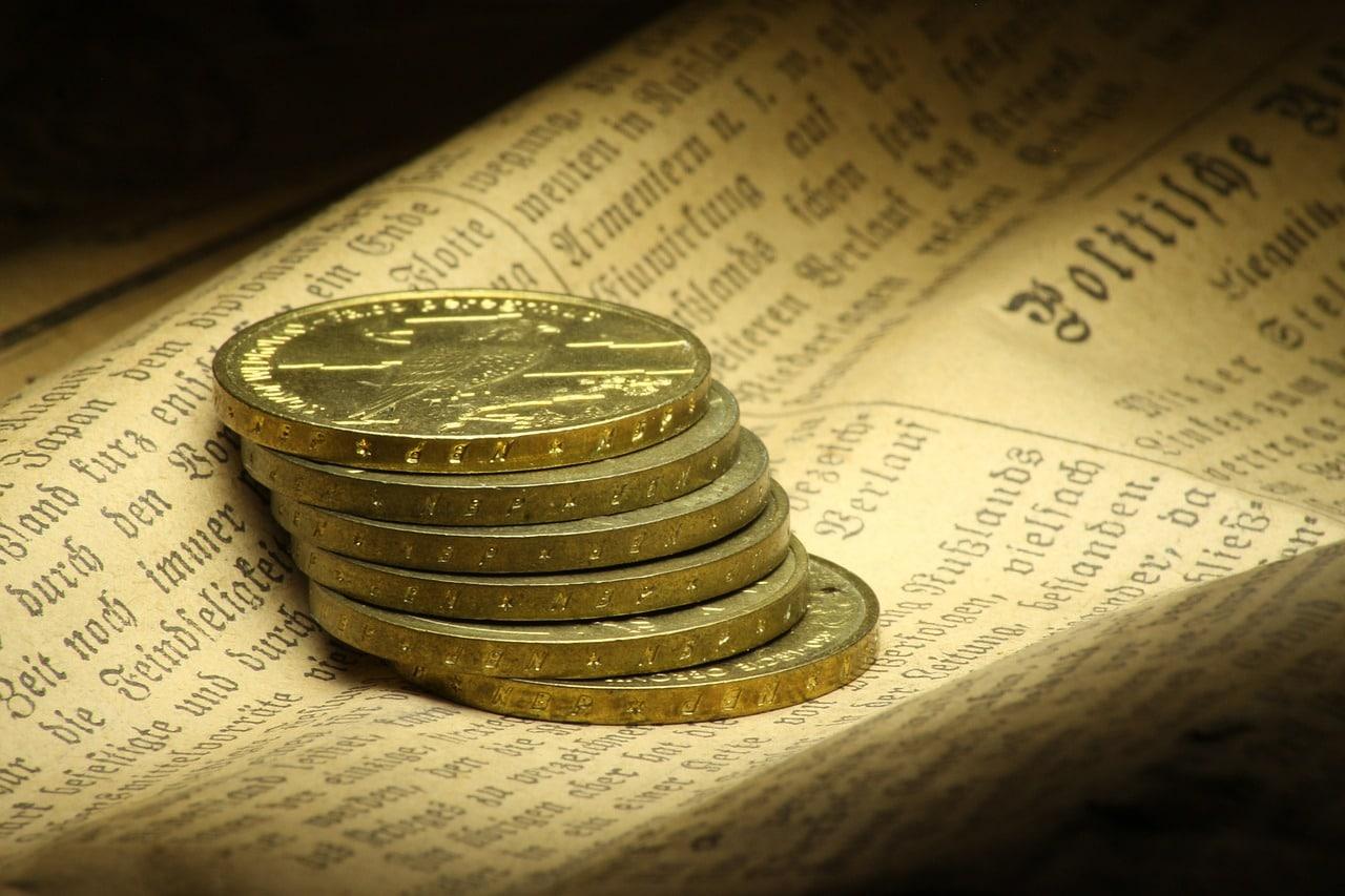 Des louis d'or posés sur un journal