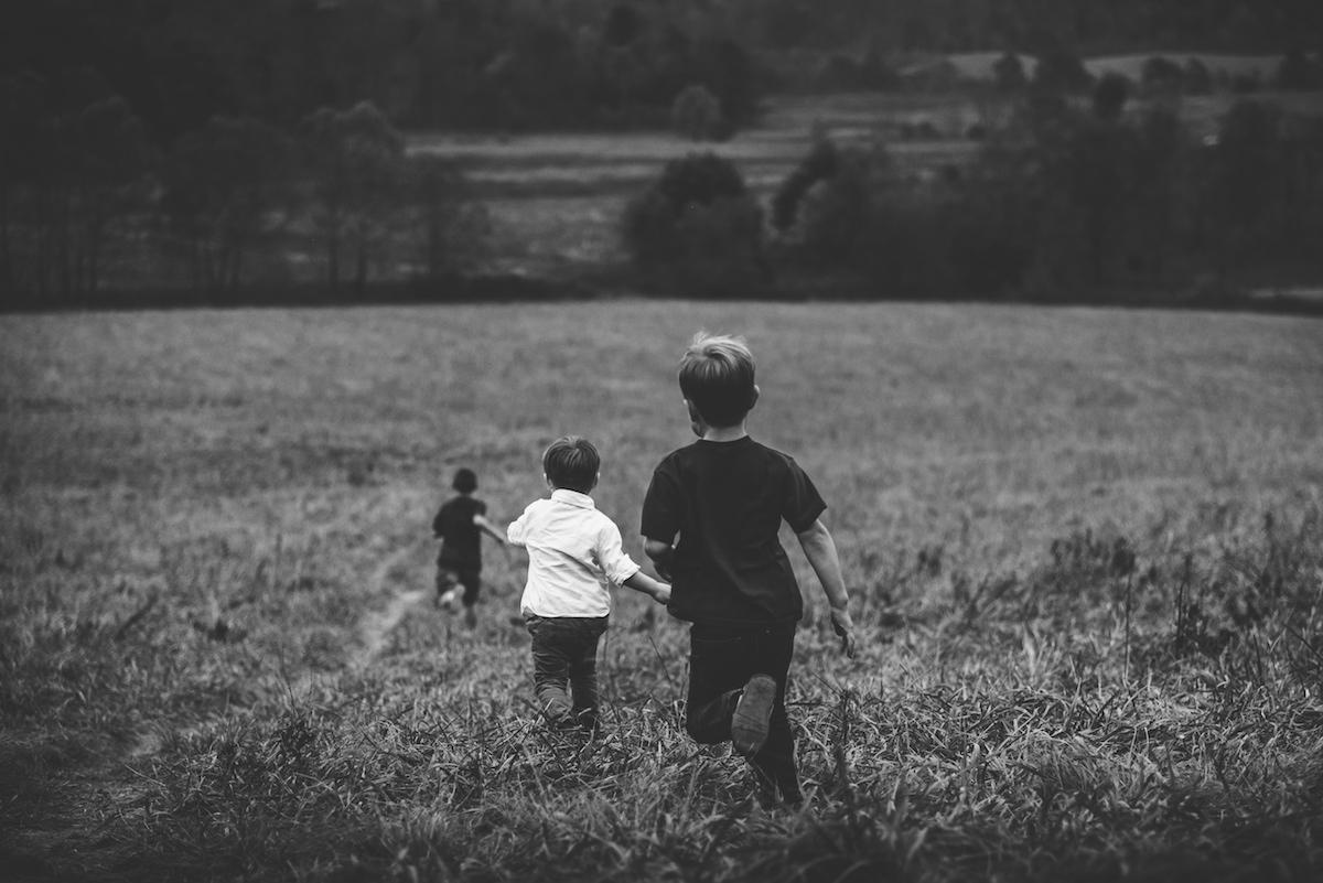Des enfants courent dans un champ en noir et blanc