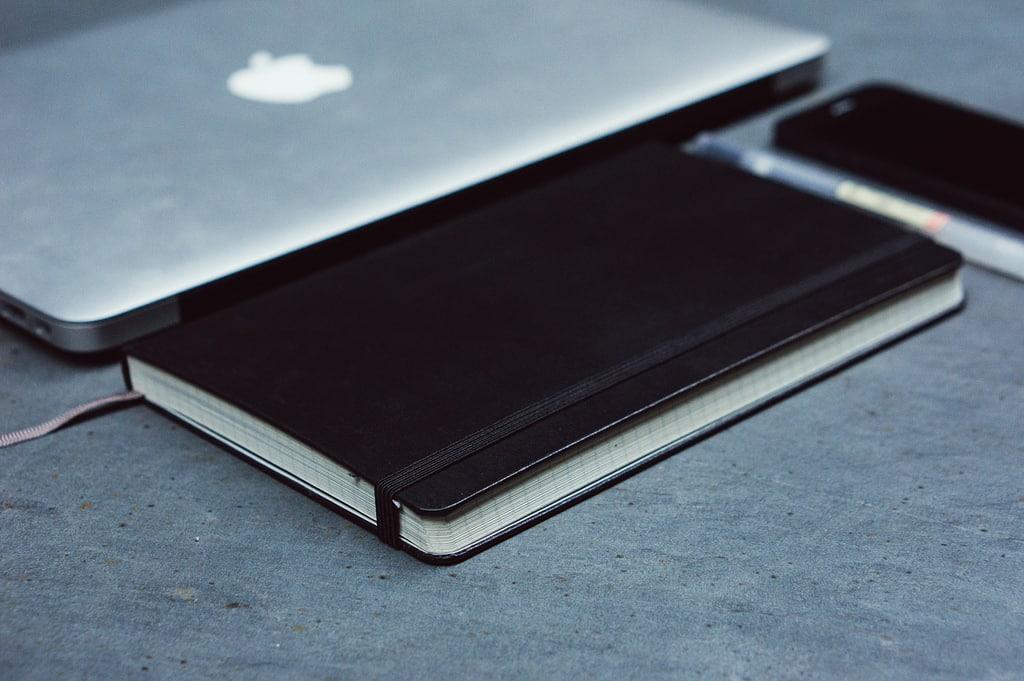 Un carnet posé à coté d'un ordinateur