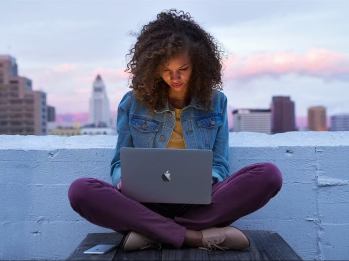 Une femme travaille sur une terasse sur son Macbook