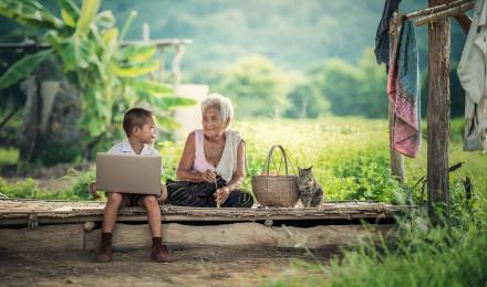 Un petit garçon tient un ordinateur à coté de sa grand mère, au Cambodge