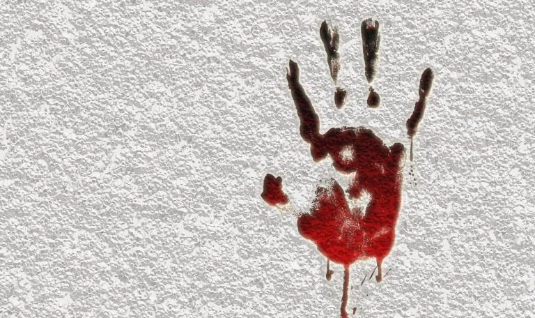Une trace de sang en forme de main contre un mur