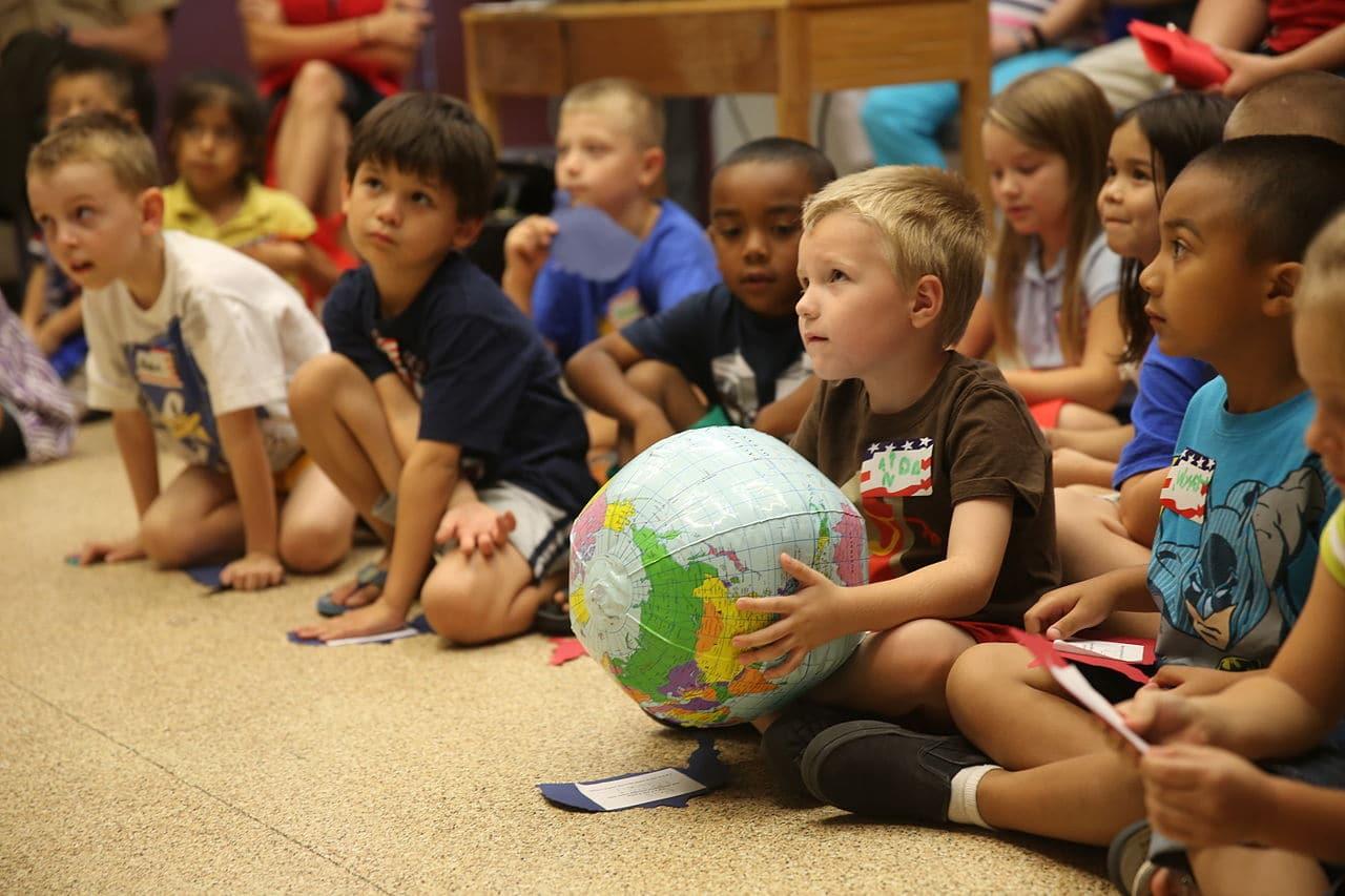 Des enfants écoutent en rond une histoire. L'un d'eux tient un globe terrestre