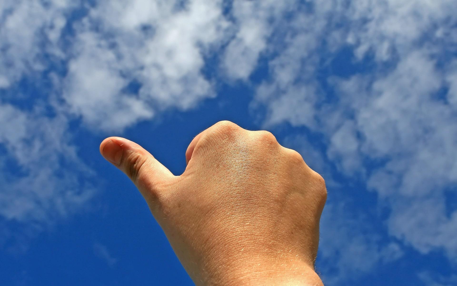Un pouce de main tendu vers le ciel bleu