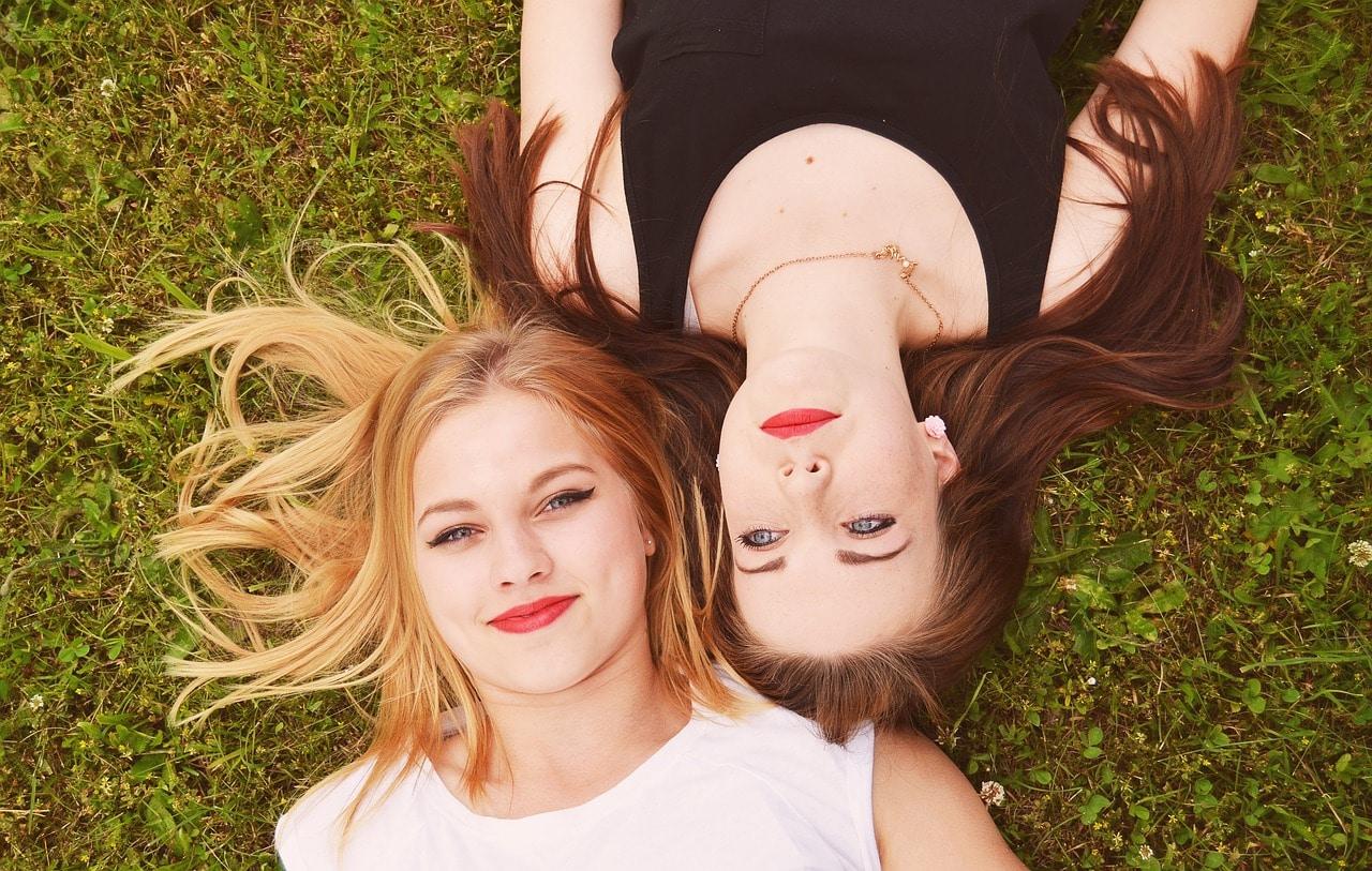 Deux femmes, une blonde et une brune, une habillée de blanc l'autre de noir