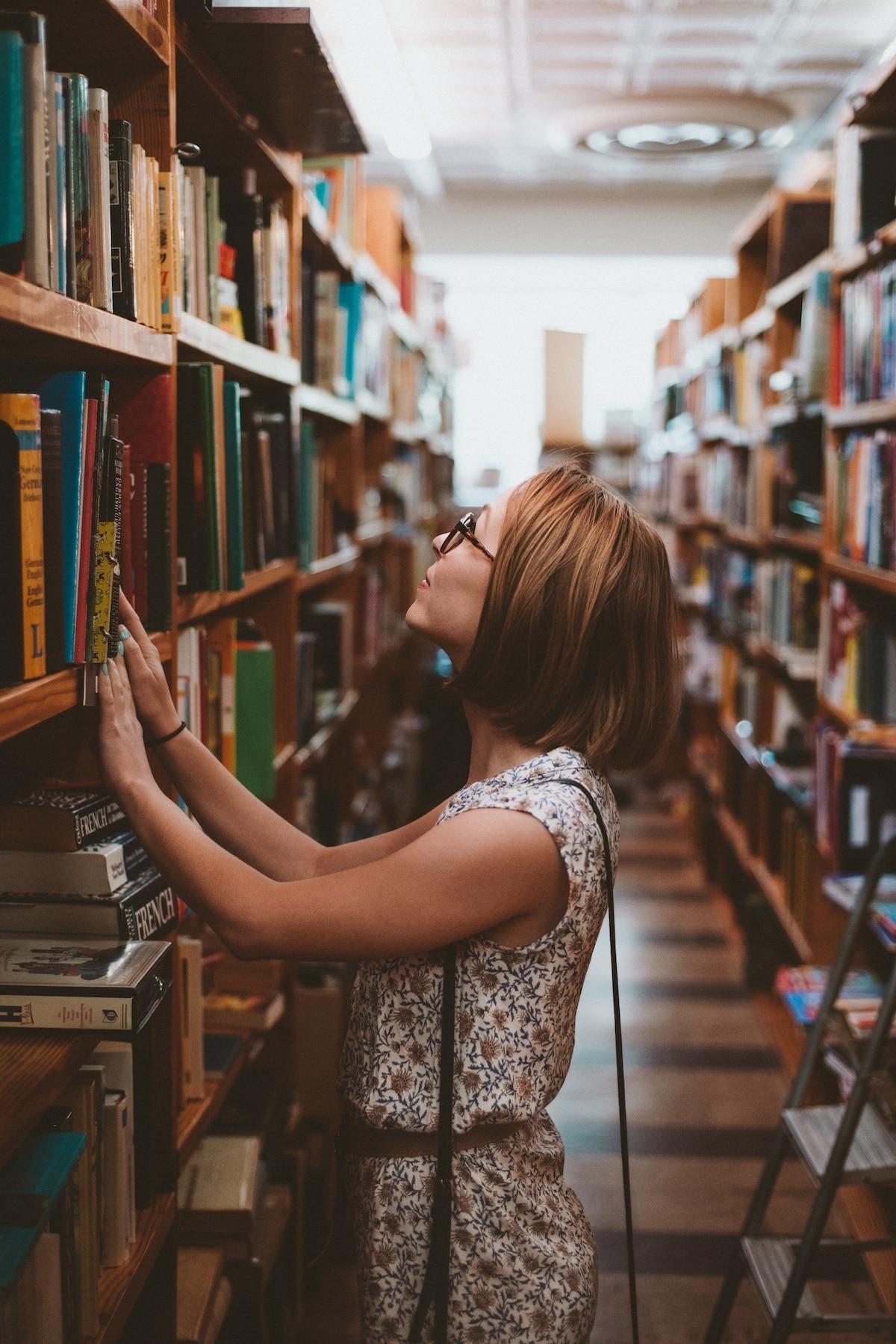 Une femme avec des lunettes parcourt les rayonnages d'une bibliothèque