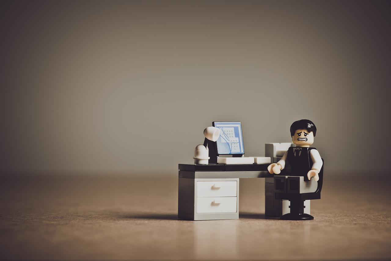 Un personnage lego grimace devant son écran d'ordinateur lego
