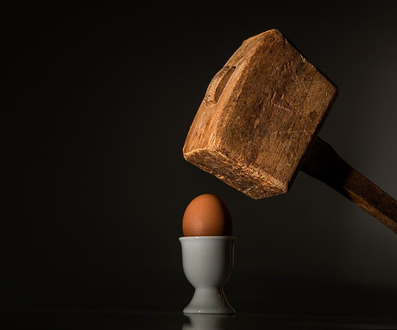 Un maillet en bois s'apprête à frapper un oeuf à la coque