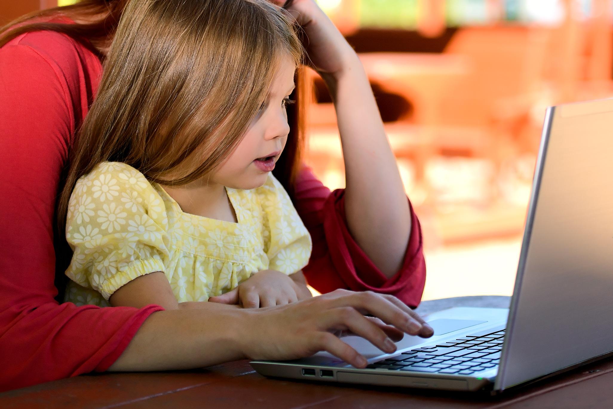 Une petite fille découvre l'informatique avec sa mère sur un ordinateur portable