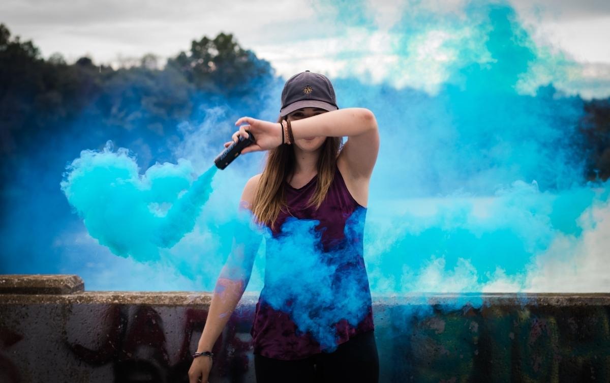 femme tient fumigène bleu