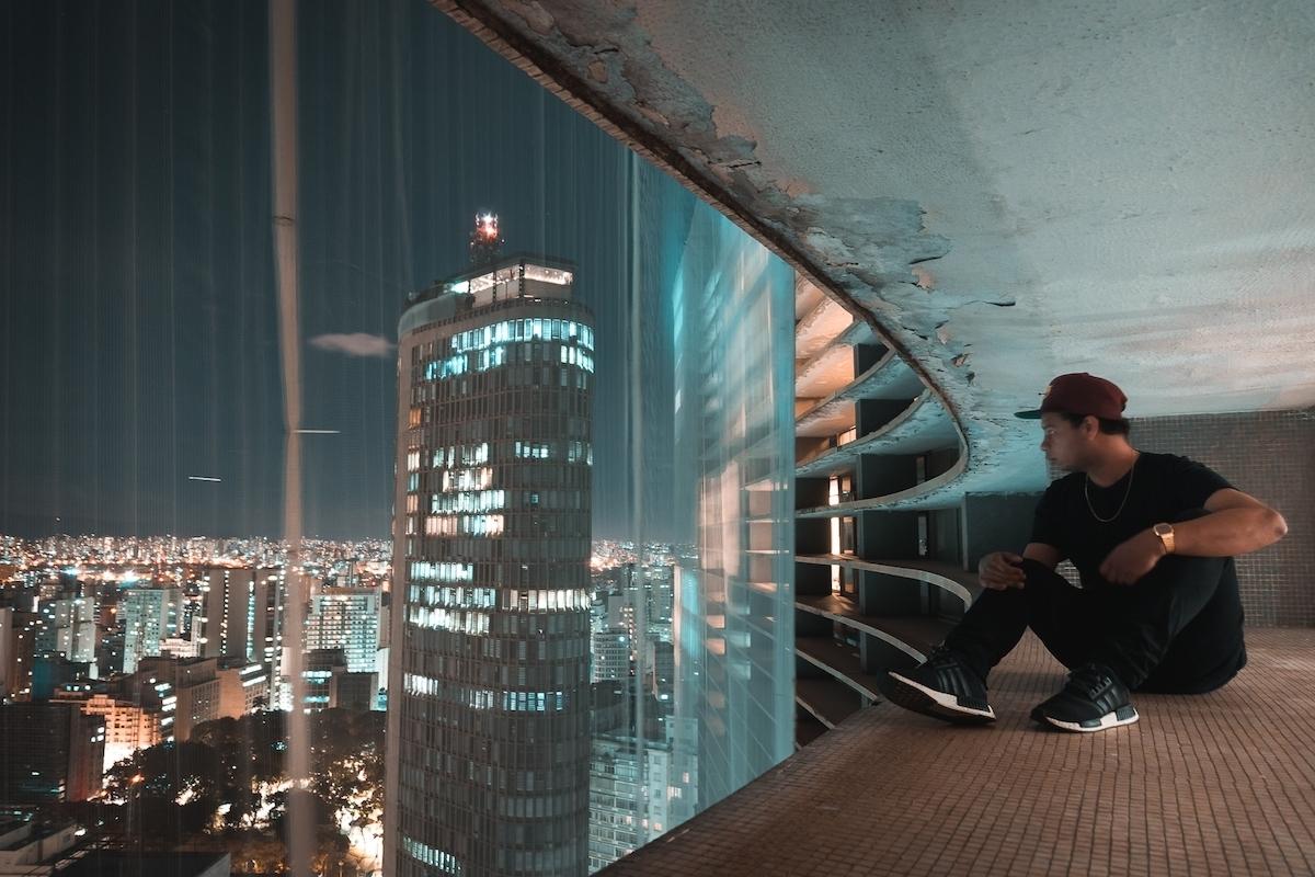 Jeune homme regarde la ville dans appartement délabré
