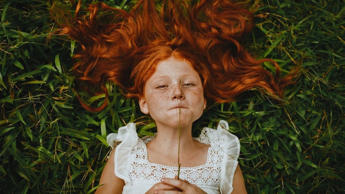 Jeune fille rousse dans l'herbe
