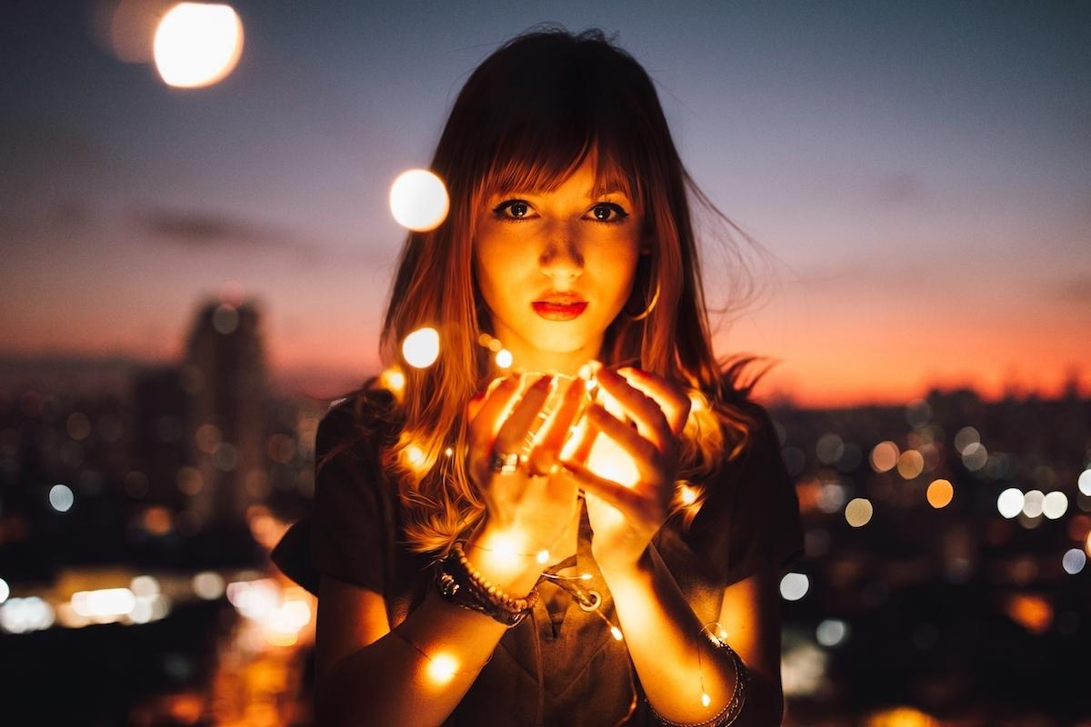 Jeune femme tient lampes dans soirée