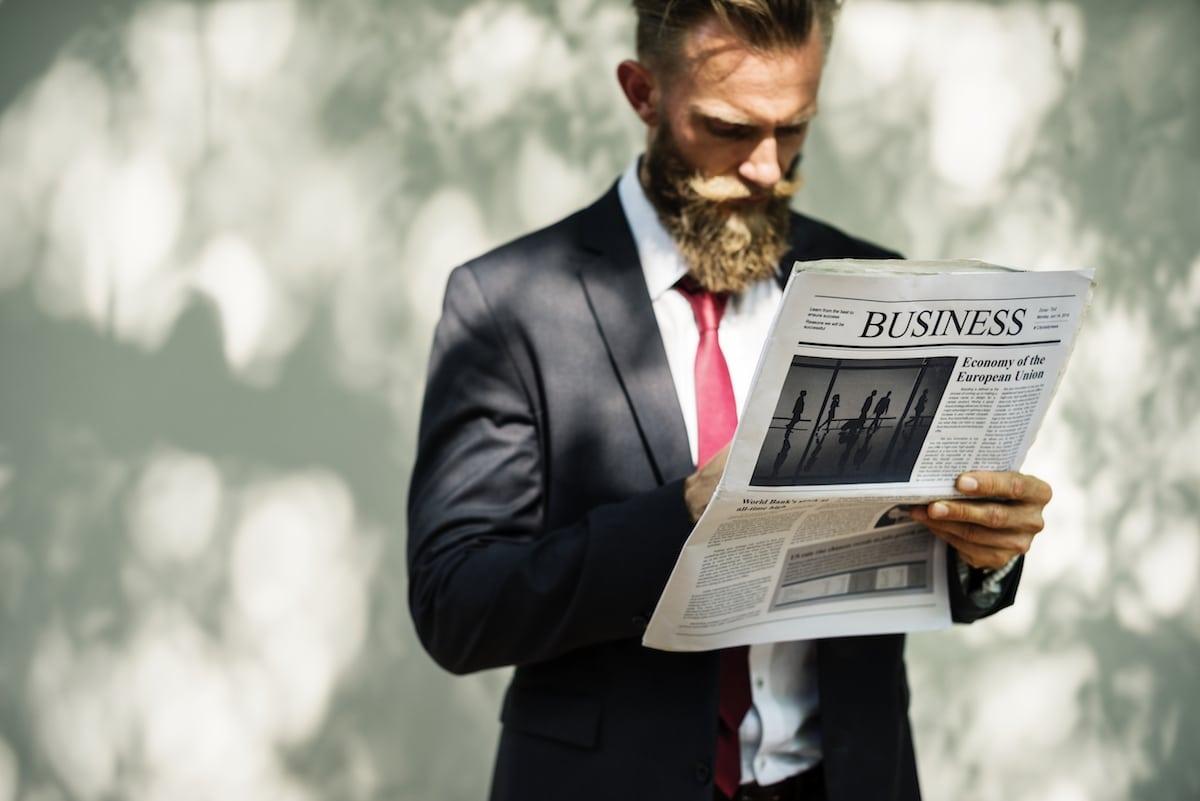 businessman barbu lit le journal