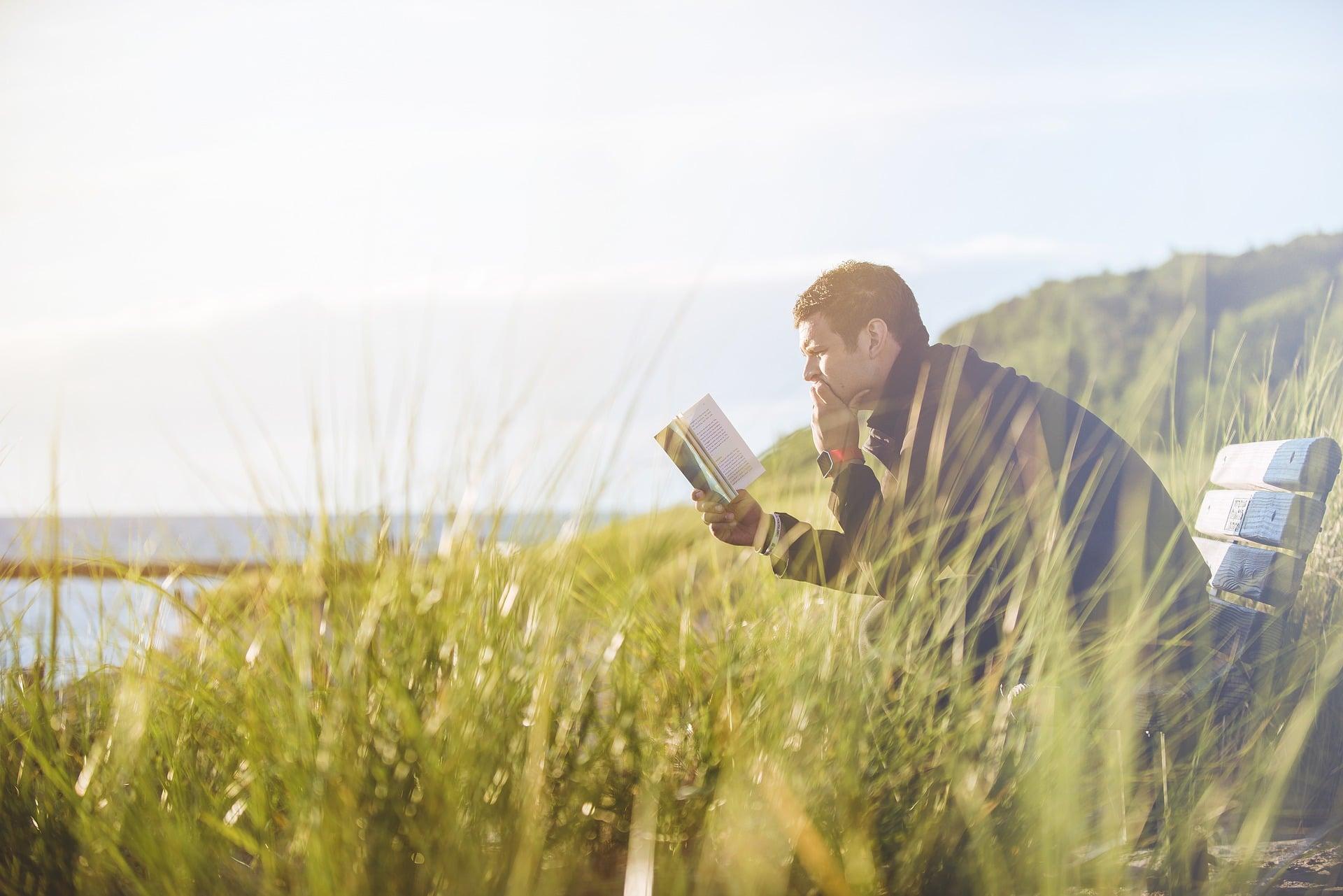 Un homme lit un livre assis dans un champ