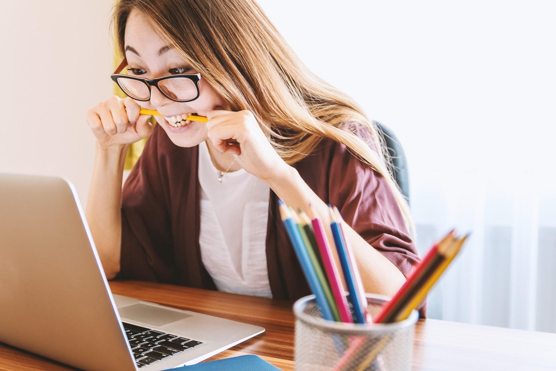 femme travaille à son bureau, crayon en bouche