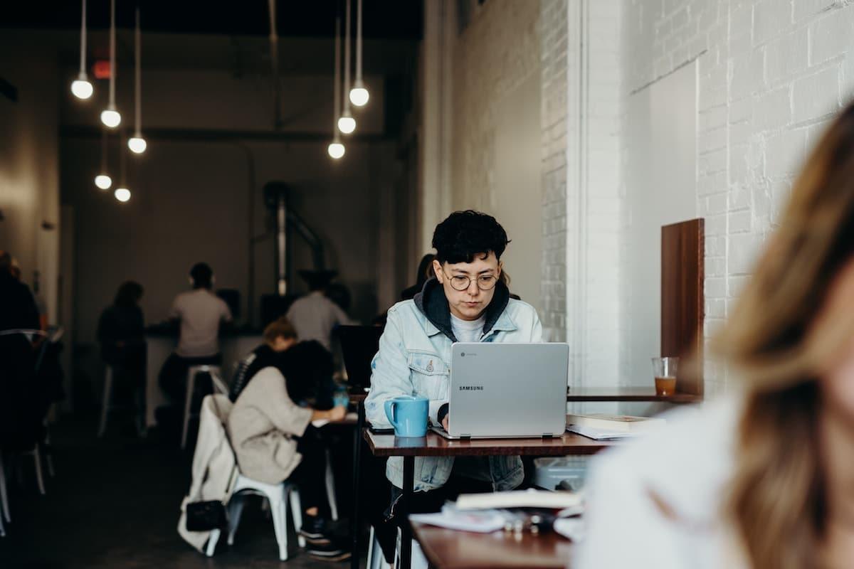 Femme dans un café travaillant à l'ordinateur