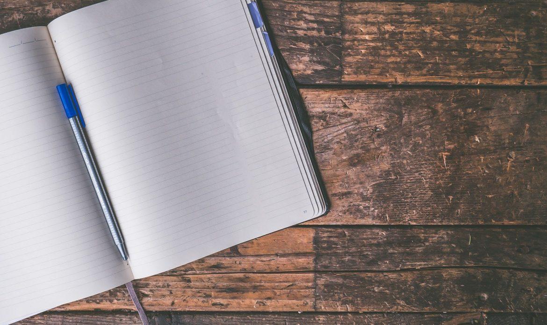 Cahier et stylo sur table en bois